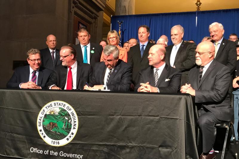 Governor Eric Holcomb, surrounding by lawmakers, signs into law a new $32 billion, two-year state budget. (Brandon Smith/IPB News)