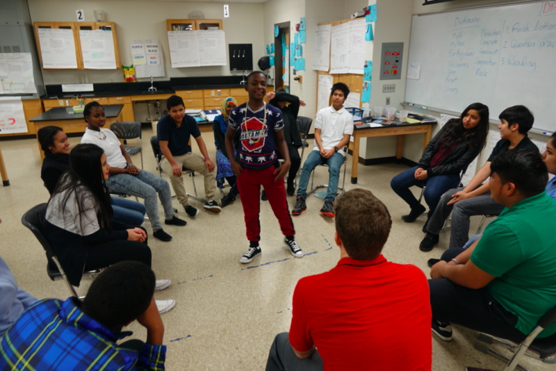 Students in Andy Slater's science class start the morning by playing a word game. Students jump up to move to an open seat if they agree with what the standing student says – sort of like musical chairs. (Eric Weddle/WFYI News)