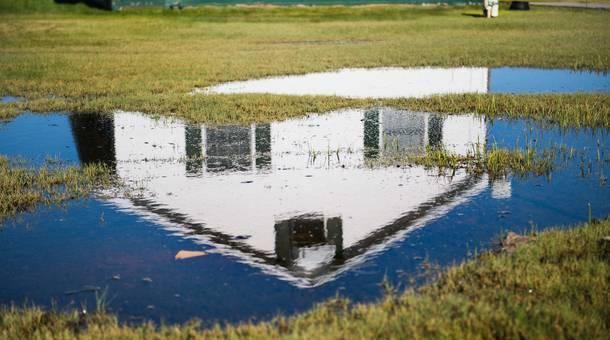 Swamp grass and standing water take over the front yard of a home in Tangier, Virginia, May 15, 2017, where climate change and rising sea levels threaten the inhabitants of the slowly sinking island.