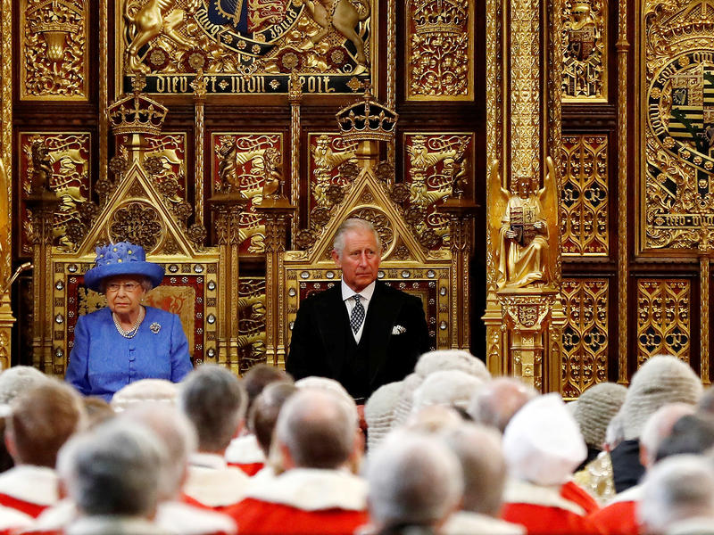 Queen Elizabeth II and Prince Charles attend the state opening of Parliament on Wednesday in London. This year, the ceremony was scaled back, with the queen arriving by car rather than carriage and not wearing the crown or robes of state.