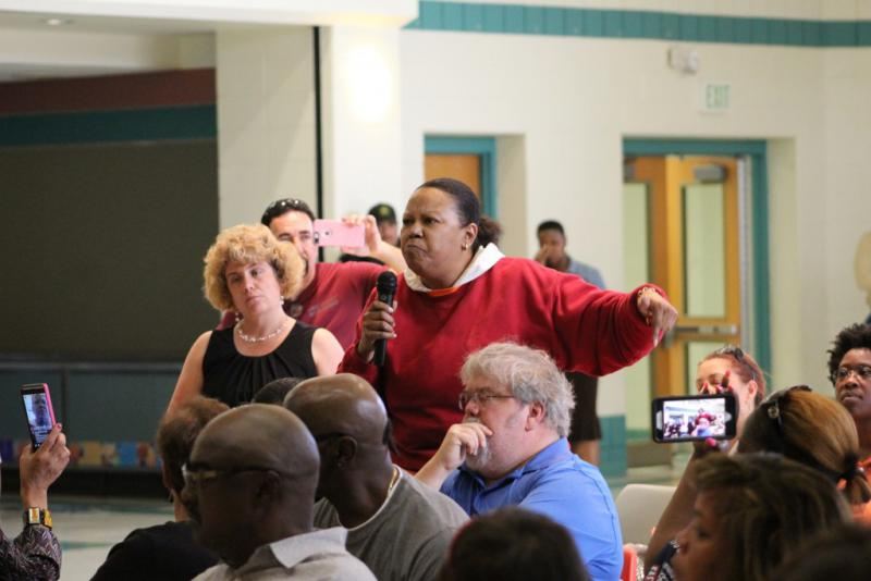 An East Chicago resident testifies at a federal public hearing on the plan to demolish West Calumet Housing Complex, as a Housing and Urban Development Official (left, in black) looks on. (Annie Ropeik/IPB News)
