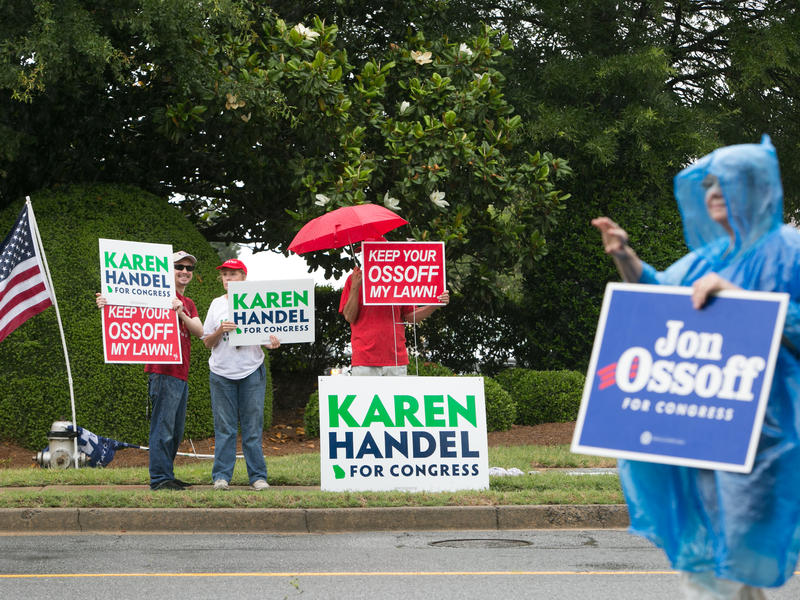 Supporters of Democrat Jon Ossoff and Republican Karen Handel campaign outside of the East Cobb Government Center on Tuesday in Marietta, Ga., on voting day for the Georgia special election.