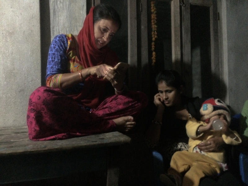 <p>After teasing her neighbors for spending too much time on their phones, Nirmala Guragain checks out her sister's iPhone, as she dozes nearby with her son.</p>