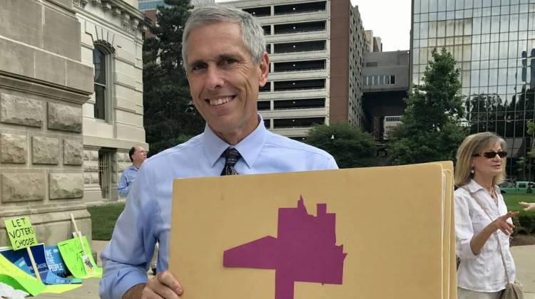 Rally attendee Greg Bowes shows off House District 99, which he says is his favorite illustration of gerrymandering in the state.
