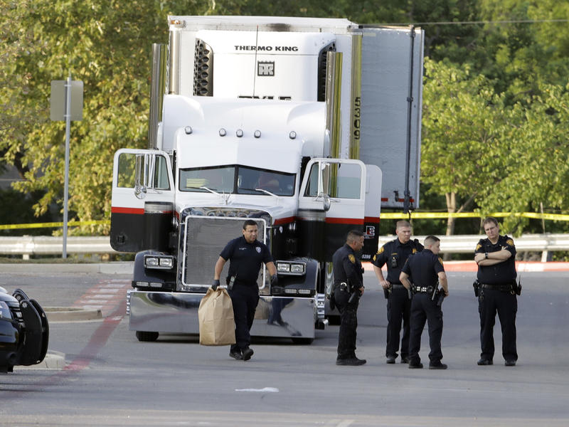 San Antonio police officers are seen in a parking lot where eight people were found dead in a tractor-trailer that contained at least 30 others outside a Walmart store.