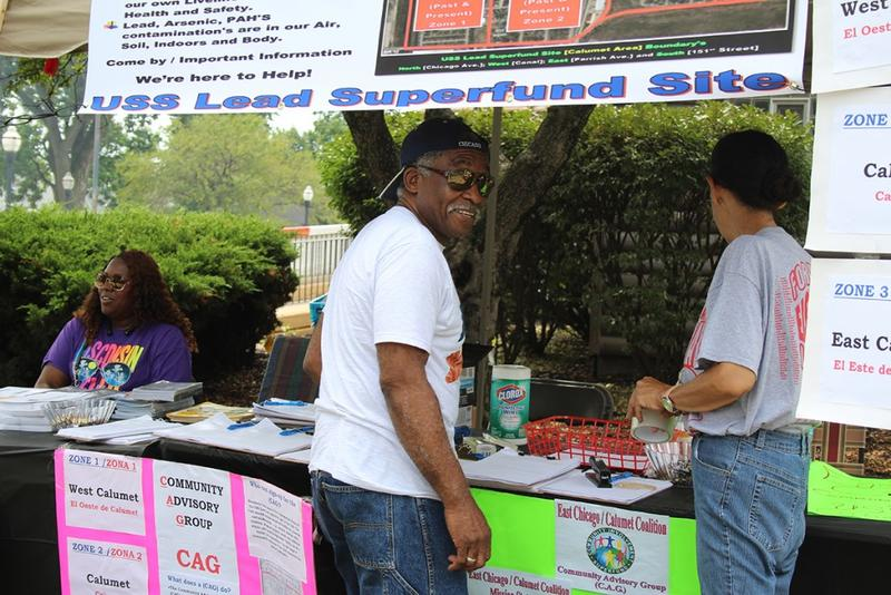 Ray Crenshaw works at the Community Advisory Group table with Akeeshea Daniels, left, and Maritza Lopez at Calumet Day, an annual block party. The CAG represents residents of the EPA administered USS Lead Superfund site in East Chicago. (Annie Ropeik/IPB