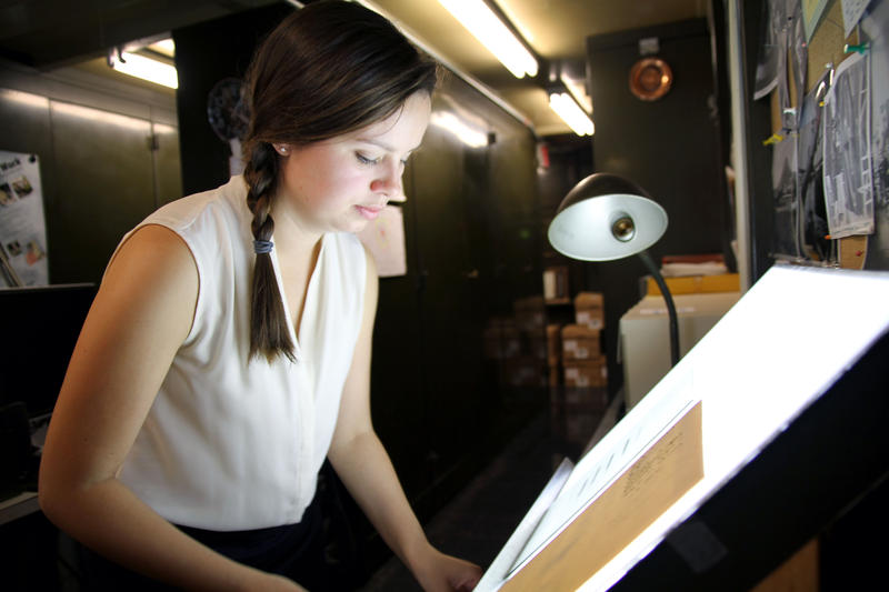 <p>Curator Lindsay Smith Zrull places a glass plate photograph of a section of the sky onto a lightbox. Smith Zrull recently discovered boxes of notebooks belonging to early women astronomers who studied the glass plates as early as 1885. </p>