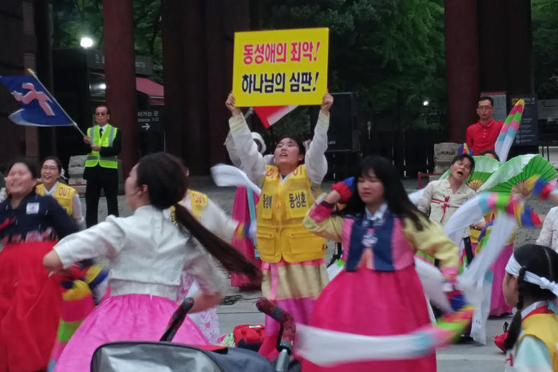 "<p>Across the street from the Korea Queer Culture Festival, protesters dance and sing while one woman jumps up and down and holds a sign that says ""Homosexuality is a crime! It's god's judgment!"" </p>"