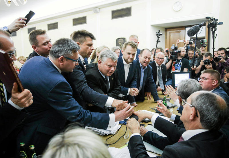 <p>Michal Szczerba of the Civic Platform party holds up a copy of the Polish Constitution as members of the parliament scuffle during the parliamentary Commission on Justice and Human Rights voting on the opposition's amendments to the bill that calls for