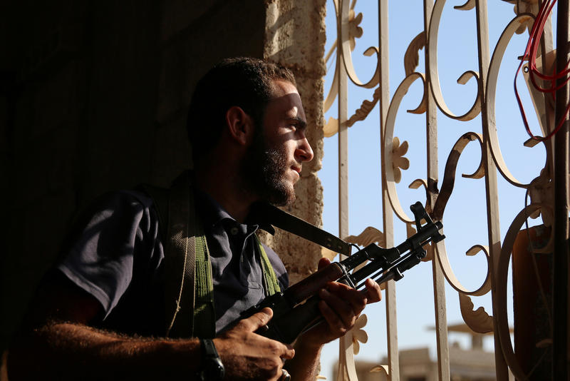 <p>A Free Syrian Army fighter looks out through a window in rebel-held Al-Yadudah village, in Deraa Governorate, Syria, on July 19.</p>