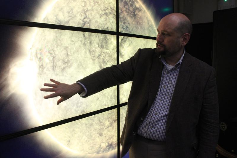 "<p>Solar astrophysicist Henry ""Trae"" Winter gestures toward a video wall depicting an image of the sun at the Harvard-Smithsonian Center for Astrophysics in Cambridge, Massachusetts.</p>"