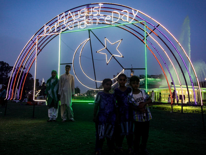 People pose in front of Pakistan Independence Day signs in Lahore. The country, created in 1947 as a homeland for South Asia's Muslims, celebrated 70 years of independence on Aug. 14.
