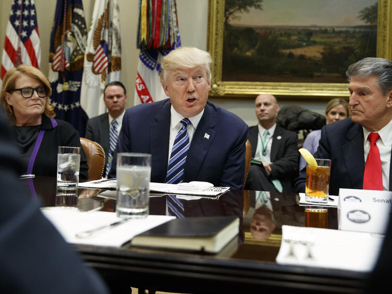 President Donald Trump, flanked by Sen. Heidi Heitkamp, D-N.D., (left) and Sen. Joe Manchin, D-W.Va., speaks during a meeting with senators on his Supreme Court Justice nominee Neil Gorsuch, on Feb. 9, 2017, in the Roosevelt Room of the White House.