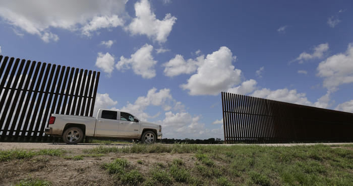 In this Sept. 15, 2015, file photo, a farmer passes along a borer fence that divides his property, Tuesday, in Mission, Texas. (AP Photo/Eric Gay)