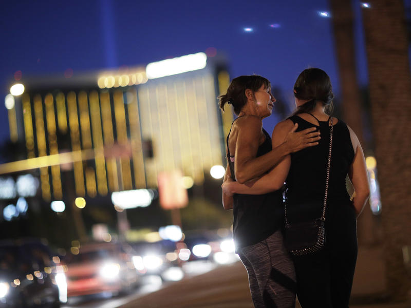 Madisen Silva, right, and Samantha Werner embrace on Friday at a makeshift memorial for victims of a mass shooting in Las Vegas. A gunman opened fire on an outdoor music concert last Sunday, killing 58 and injuring hundreds.