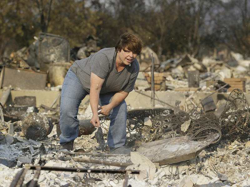 Resident Tammy Christiansen searches the remains of her Coffey Park neighborhood home in Santa Rosa.