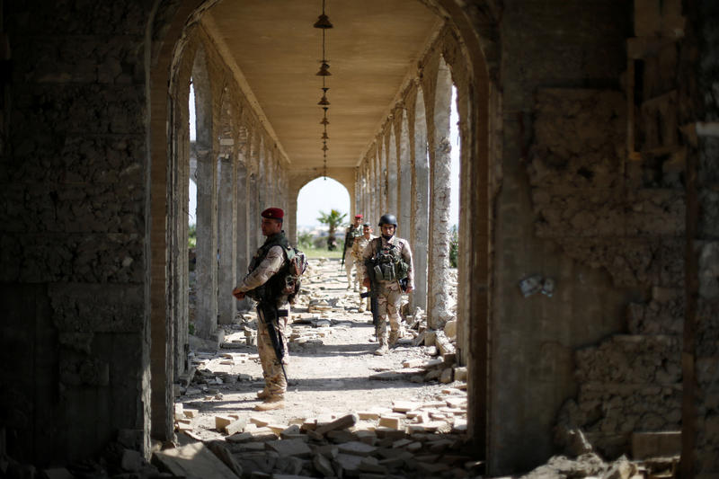 <p>Members of the Iraqi security forces stand guard as Ameen Mukdad, a violinist from Mosul who lived under ISIS's rule for two and a half years, performs at Nabi Yunus shrine in eastern Mosul. </p>