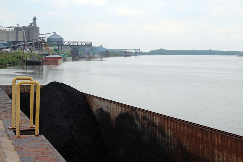 A barge of petcoke, a petroleum byproduct used to make aluminum, waits for offloading at the Port of Indiana-Mt. Vernon, with other barges carrying fertilizer, cement and soybean oil lined up on the Ohio River bank. (Annie Ropeik/IPB News)