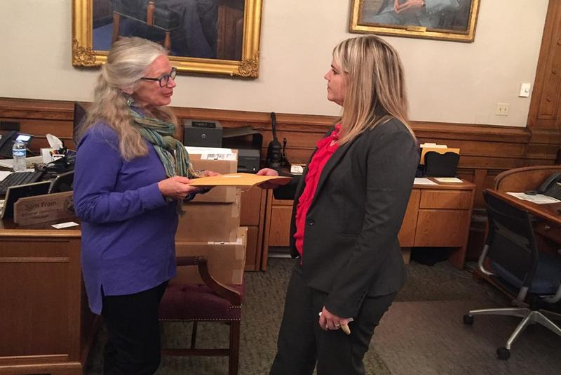 Dr. Leslie Bishop delivers a letter asking Gov. Holcomb to reduce logging on state land to Rebecca Holwerda, the governor's director of operations. (Courtesy of Indiana Forest Alliance)