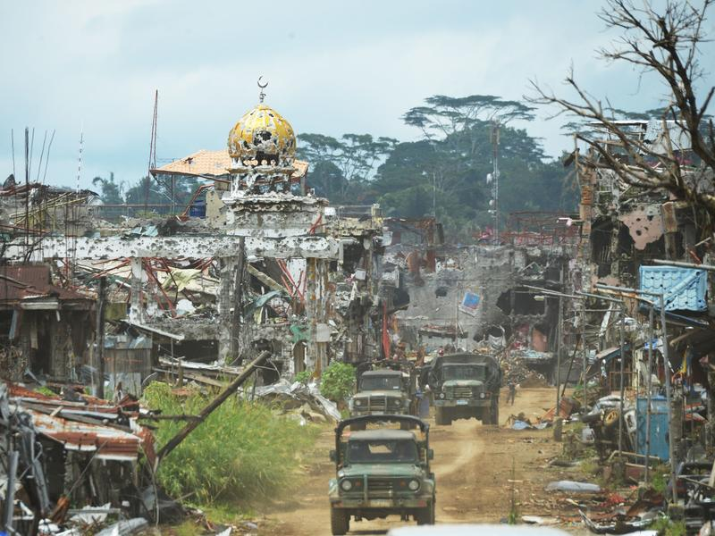 Military trucks drive past destroyed buildings and a mosque in what had been the center of fighting in Marawi on the southern Philippine island of Mindanao on Oct. 25, days after the military declared that the battle against ISIS-linked militants was over