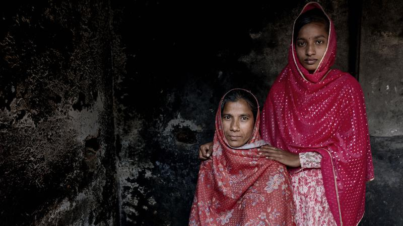 <p>Mother and daughter, Rongmala Begum (standing) and Mayna Begum, are shown at their home outside of Dhaka, Bangladesh.</p>