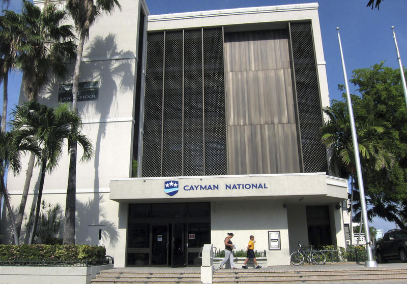 <p>People walk out of a branch of the Cayman National Bank in George Town, Cayman Islands.</p>