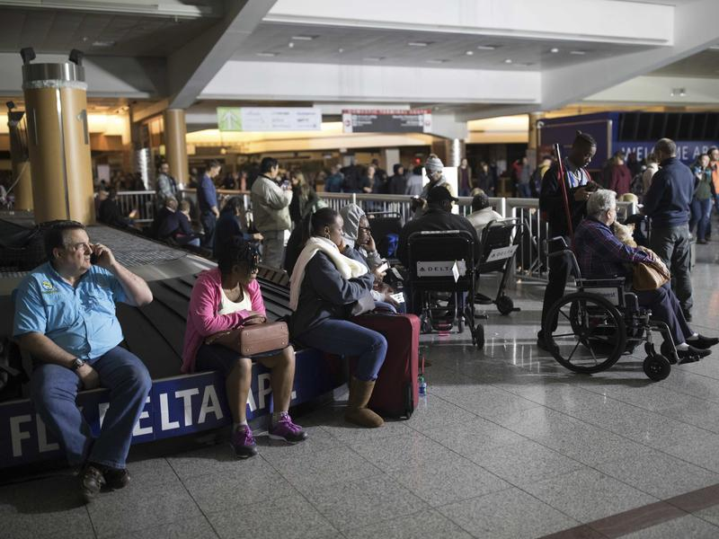 Passengers wait after the lights went out at Hartfield-Jackson Atlanta International Airport on Sunday. Many travelers were stuck in grounded planes for hours.