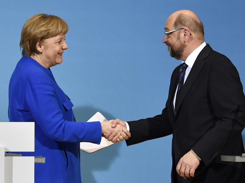 German Chancellor Angela Merkel shakes hands Friday with the leader of the Social Democratic Party, Martin Schulz. Merkel's conservatives reached a
