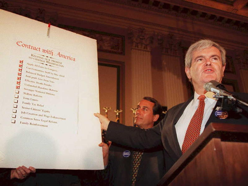 """Newt Gingrich, then speaker of the House in 1994, holds up a copy of the Republican Party's """"Contract With America."""""""