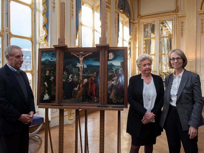 Standingwith French Culture Minister Françoise Nyssen, Christopher Bromberg and Henrietta Schubert, grandchildren of Henry and Hertha Bromberg, view Flemish painter Joachim Patinir's Triptych of the Crucifixion, which was returned to them Monday by the Fr