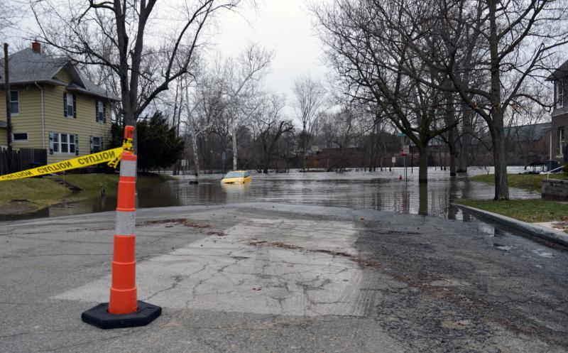 Water covers a street near the St. Joseph River in South Bend. A yellow hatchback sits with water up to its windows