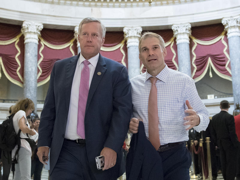 """Rep. Mark Meadows, R-N.C. (left), chairman of the conservative House Freedom Caucus, and Rep. Jim Jordan, R-Ohio, a key member of the group, walk through Statuary Hall at the Capitol last September. Meadows says a vote on immigration will be a """"defining m"""