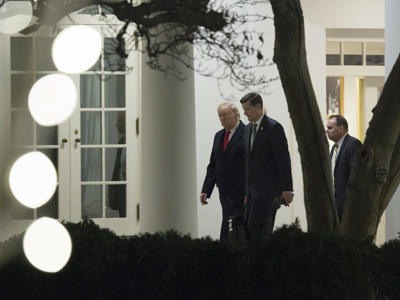 President Trump speaks with White House secretary Rob Porter (center) and Sen. Mike Lee, R-Utah, outside the White House in December. Porter resigned this week amid allegations of domestic violence against his ex-wives.