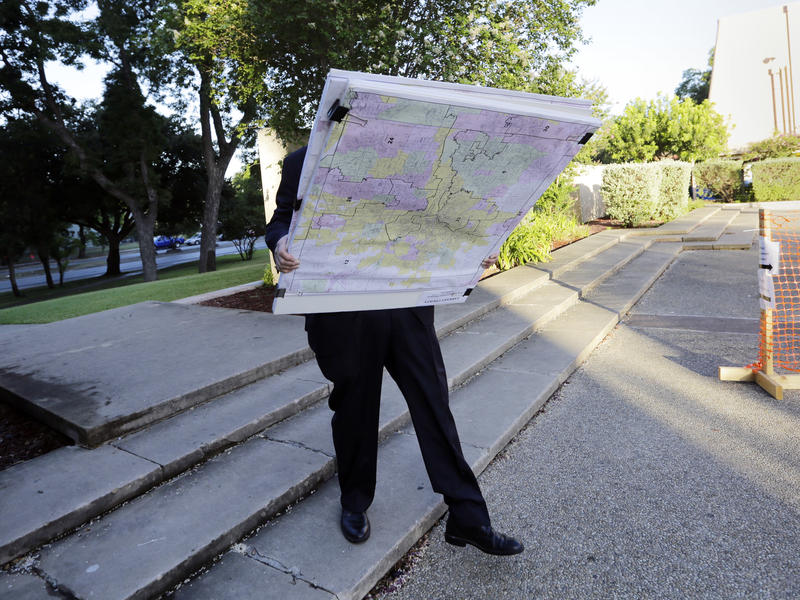 A man with a set of maps heads to a federal courthouse in San Antonio last year for a redistricting trial. Texas is one of three states with cases in redistricting before the Supreme Court.