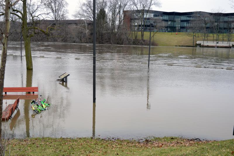 Water covers a railing, benches and a bike in Howard Park