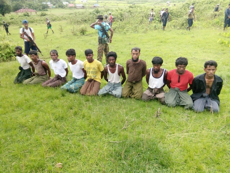 Ten Rohingya Muslim men kneel with their hands bound as members of the Myanmar security forces stand guard in Inn Din village on Sept. 2, 2017. The photo has been published as part of an extensive Reuters investigation into the massacre of the 10 men, who