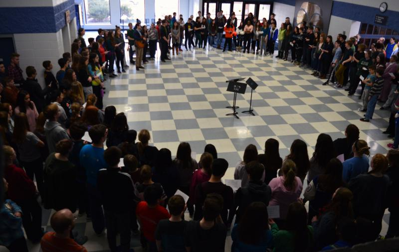 about 300 students gather in a circle listening to one talk