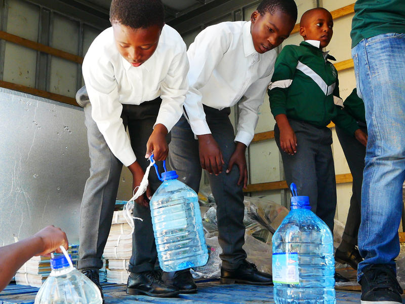 Schoolboys unload donated water at the Isikhokelo Primary School in Khayelitsha township. The principal shut off most taps to keep to tight water restrictions and has told students to bring their own water.