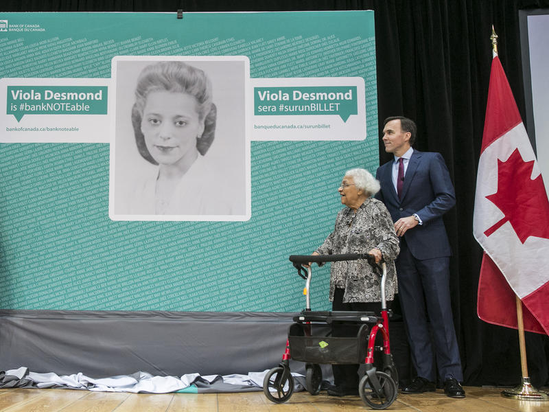 """Stephen Poloz, governor of the Bank of Canada, from left, Patty Hajdu, Canada's status of women minister, William """"Bill"""" Morneau, Canada's finance minister, and Wanda Robson, sister of Viola Desmond, reveal a photograph of Desmond on stage during an event"""
