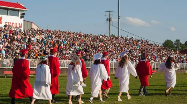 Students walk in a graduation ceremony.