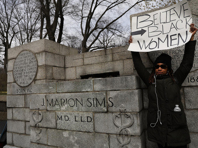 A woman stands beside the empty pedestal where a statue of J. Marion Sims used to stand. Multiple groups demanded the removal of the statue, which sat on a pedestal praising his achievements as