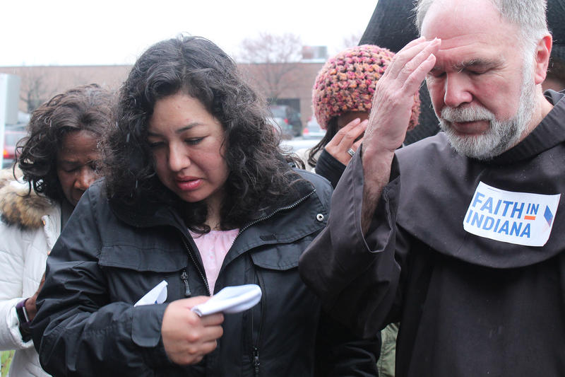After her check-in, Erika Fierro holds back tears while praying with her pastor, Father Larry Janezic. (Lauren Chapman/IPB News)