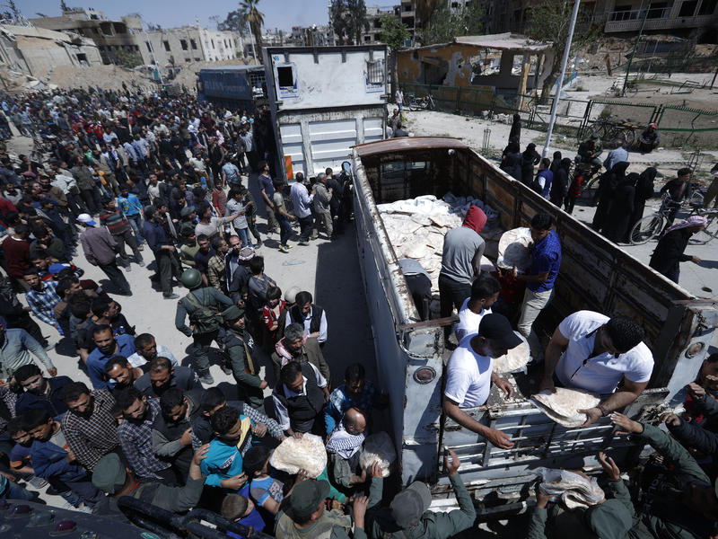 Syrian authorities distribute bread, vegetables and pasta to residents on Monday in the town of Douma, the site of a suspected chemical weapons attack, near Damascus, Syria.