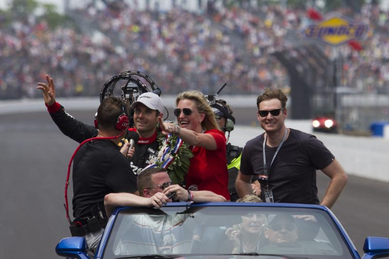 Will Power waves to the crowd with his wife, Elizabeth, during the victory lap after winning the Indianapolis 500 on Sunday. (Doug Jaggers/WFYI News)