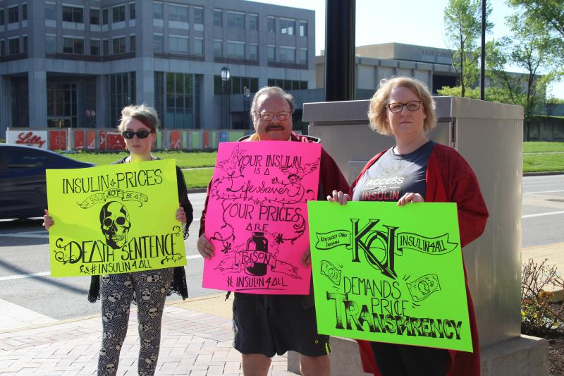 Mackenzie Fields, Dan Meno and Eryn Ruder hold signs on the street across from Eli Lilly prior to the shareholder meeting. Fields illustrated all three of the signs. (Samantha Horton/IPB News)