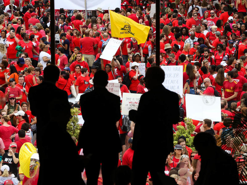 People inside the North Carolina state Capitol, in Raleigh, look out a window upon the teachers' march Wednesday. Educators, school workers and parents joined the protests to push for greater school funding.