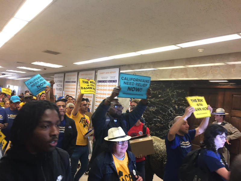 Supporters of a November ballot initiative to repeal the California law that limits local rent control ordinances march past Gov. Jerry Brown's office on Thursday, June 21, 2018, after attending a legislative hearing on the measure.