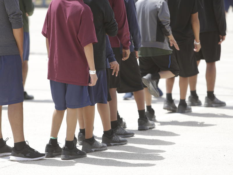 Boys, ages 10 to 17, stand outside a government-contracted youth shelter in Brownsville, Texas. Ninety percent of the residents traveled to the United States alone seeking protection; the remainder were separated from their families at the border under a