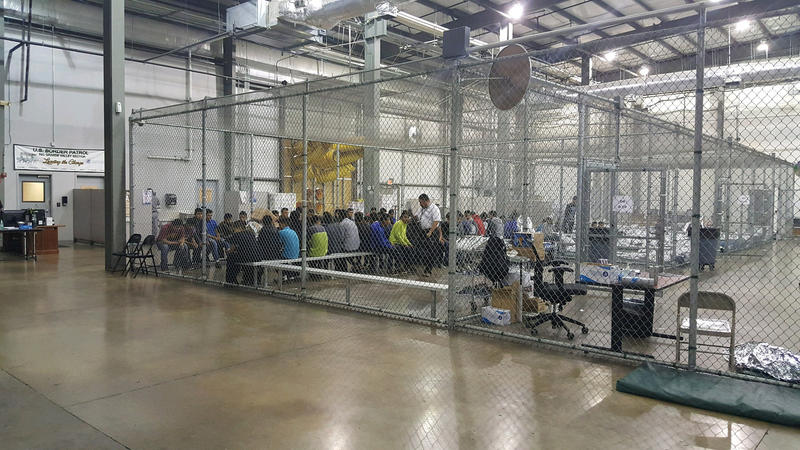 Detainees being housed inside fenced rooms at a government facility.