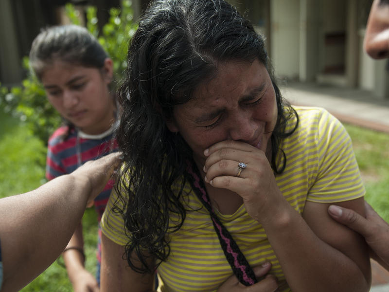 Lilian Hernandez cries as she is comforted by her husband at the Mormon church that has been enabled as a shelter near Escuintla, Guatemala, on Tuesday. Hernandez lost 36 family members in all, missing and presumed dead in the town of San Miguel Los Lotes